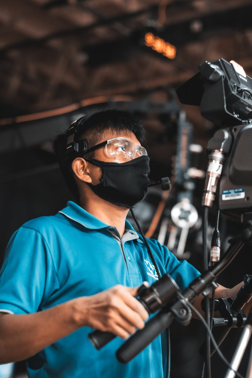 cameraman in protective mask and glasses filming video